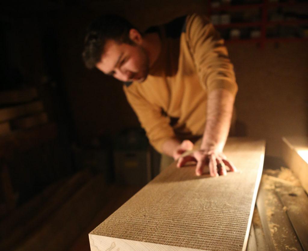 Silvain Hoeh en train de travailler sur une pièce de bois.